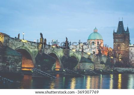 The Charles Bridge (Czech: Karluv Most) is a famous historic bridge that crosses the Vltava river in Prague, Czech Republic. Vintage filter applied. - stock photo