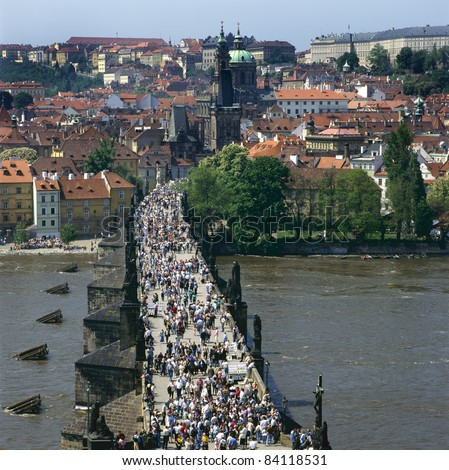 The Charles Bridge over the Vltava river,built in baroque style, in Prague is always crowded with tourists, artists and musicians. The other side of the bridge is called Mala Strana. - stock photo