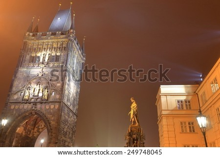 The Charles IV statue and Gothic tower in foggy autumn evening, Prague, Czech Republic - stock photo
