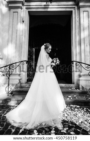 The charming bride stands on the stairs