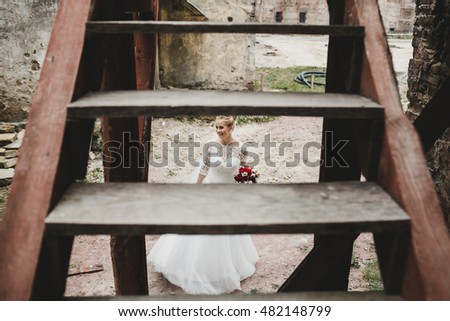 The charming bride stands under stairs