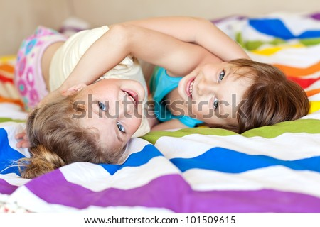 The charming children playing on the bed at home - stock photo
