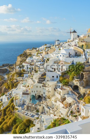 The charming Greek village of Oia in the evening, just before sunset.The view from the height above the houses, villas and the Mediterranean sea.Santorini (Thira) island.Cyclades.Greece.Europe. - stock photo
