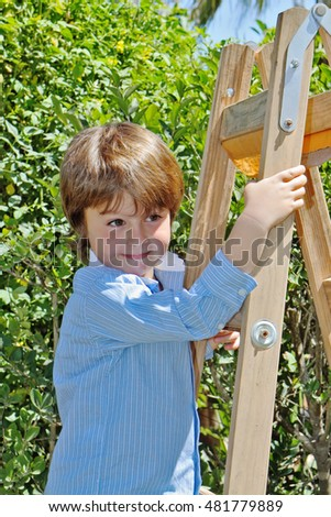 The charming little boy with a smile poses on step-ladder. In the background - spring green hedges