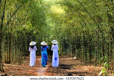 The charming slender girl in traditional ao dai Vietnam goes in bamboo forest.