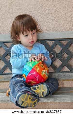 The charming thoughtful  little boy in dark blue jeans and blue sweater sits on to a garden bench with a bright multi-coloured ball in hands - stock photo