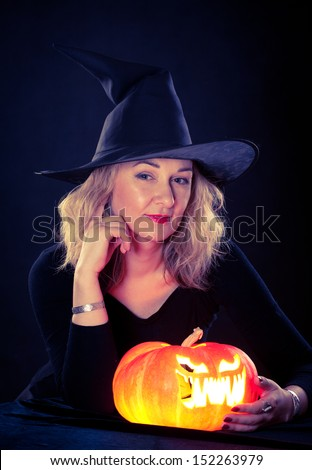 The charming witch cooks the potion on the eve of Halloween.