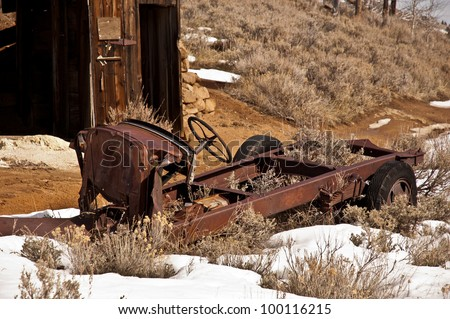 The chassis of an old car sits across the road from the ruins of a garage that once served a deserted mining community - stock photo