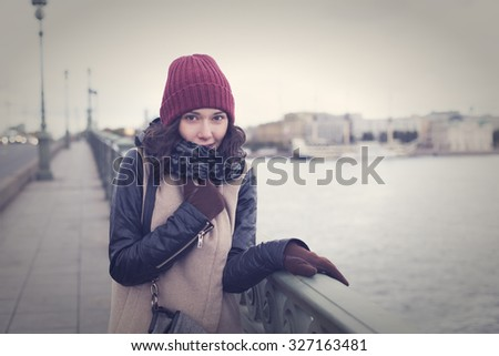 The cheerful beautiful girl in a leather jacket freezes on the bridge in St. Petersburg - stock photo