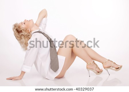 The cheerful beautiful young woman sitting on a floor
