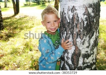 The cheerful boy embracing a trunk of a birch. - stock photo