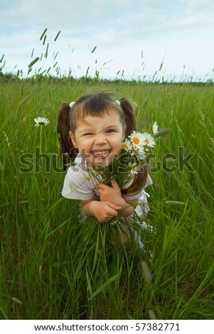 The cheerful child embraces wild flowers in the field - stock photo
