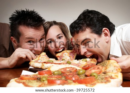 The cheerful company of youth eating a pizza - stock photo