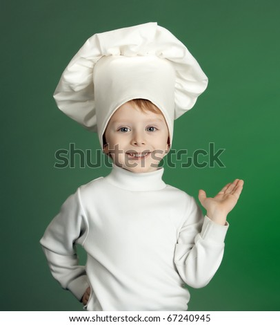 The cheerful little boy in a suit of the cook costs with the lifted hand - stock photo