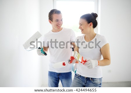 The cheerful young couple is engaged in coloring of walls in the room. They stand and look at each other. Both smile. They hold rollers and a brush for coloring in hand. Behind their backs a window. - stock photo