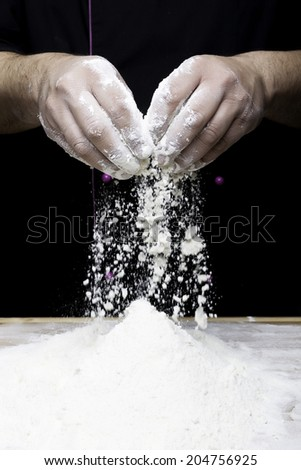 the chef hands are dropping flour over a wooden table - stock photo