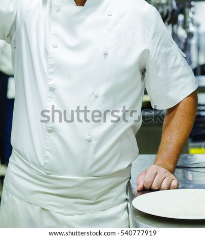 The chef in the kitchen, the white uniform and the chief posture.