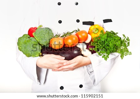 The chef is holding two arms full of vegetables fresh from the garden. Broccoli, red pepper, tomatoes on the vine, eggplant, mushrooms, yellow pepper and parsley.