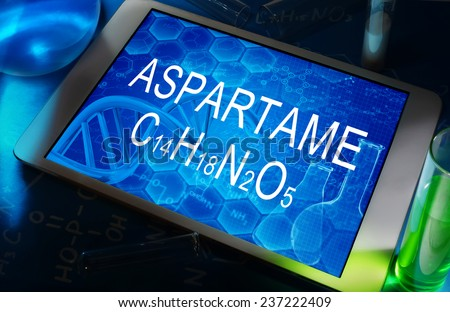the chemical formula of aspartame on a tablet with test tubes   - stock photo