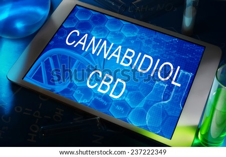 the chemical formula of cannabidiol on a tablet with test tubes   - stock photo