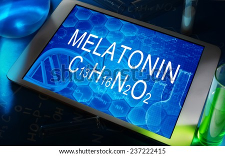 the chemical formula of melatonin on a tablet with test tubes   - stock photo