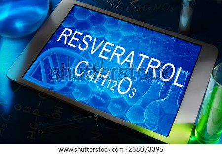 the chemical formula of Resveratrol on a tablet with test tubes   - stock photo