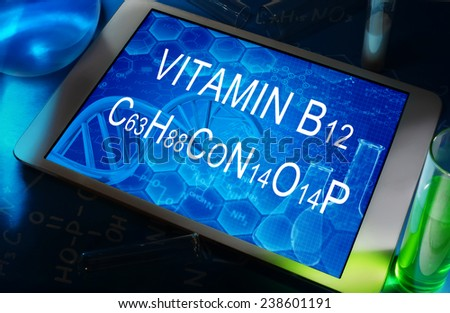 the chemical formula Vitamin B12 on a tablet with test tubes   - stock photo
