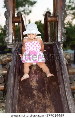 The child, a little girl goes for a drive on a swing in the playground, summer vacation, carefree childhood, education and children's activities - stock photo