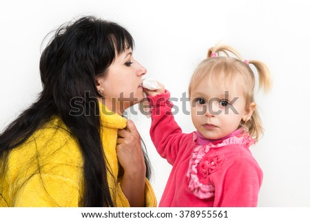 The child, a little girl my mother wiping the face with a napkin, raising children, caring for relatives, care and treatment, the symptoms of colds, influenza, allergies. - stock photo