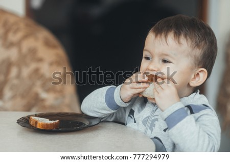 the child at the table eating a sandwich with sausage and cheese, just bread