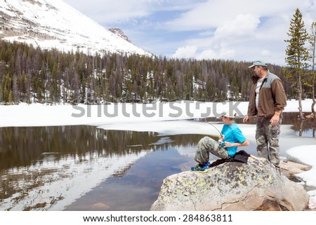 The child caught a fish in a mountain lake. Father ready to help.  Mirror Lake,  Uinta-Wasatch-Cache National Forest, Utah - stock photo