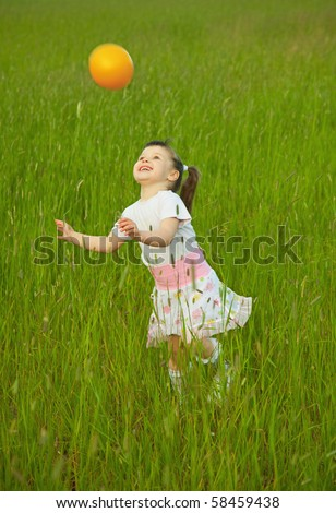 The child cheerfully plays with a ball in the field - stock photo