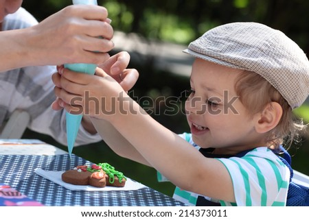 The child coloring gingerbread at the workshop - stock photo