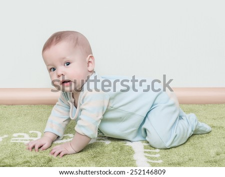 The child creeps on a soft green carpet isolated - stock photo