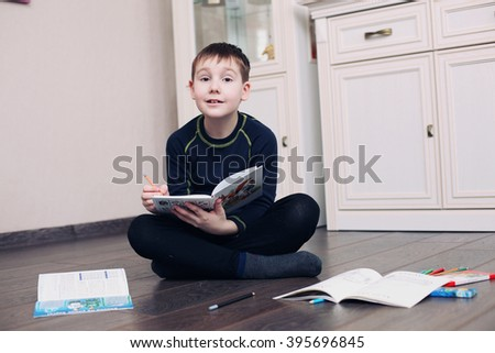 the child does homework at home on a floor with book