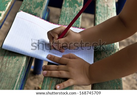 The child draws on a street bench in a notebook owl