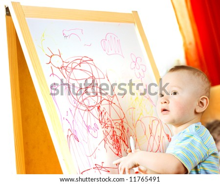 The child draws on the board