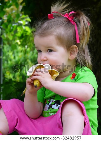 The child eats a banana. - stock photo