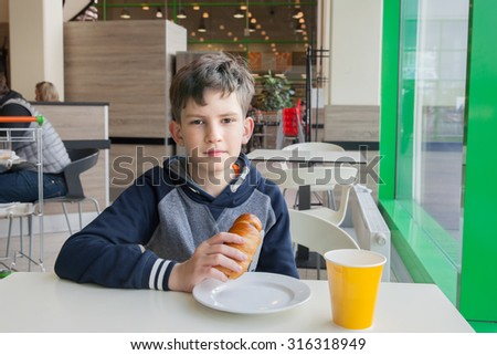 the child eats in the school cafeteria    - stock photo