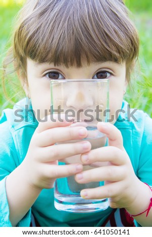 the child holds a glass of water in his hands. selective focus.