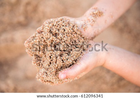 The child holds sand in the hands of the beach near the sea