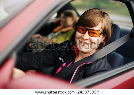 The child in a safety seat near to mother who sits on forward sitting of the car. - stock photo