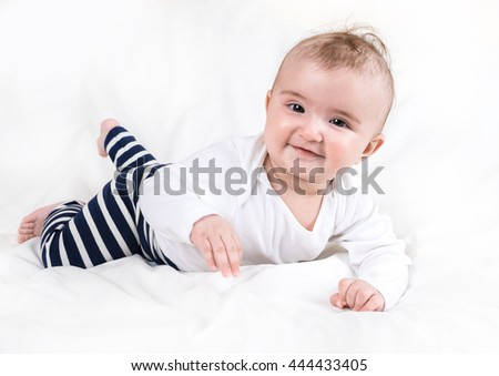 The child in bright clothes and diapers on a white background