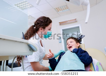 The child in dentist's chair with a female doctor