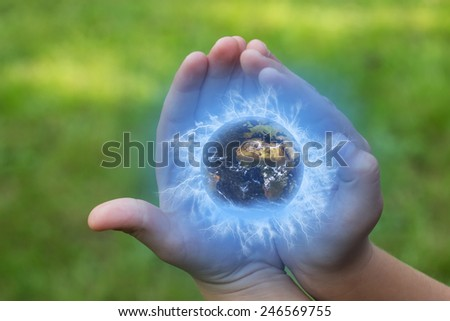 The child is holding a globe in his hands outdoors.Green lawn in the background. Elements of this image furnished by NASA, - stock photo