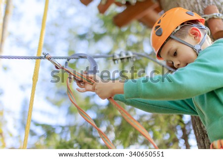 the child is ready to go through an obstacle course in a rope park. courageous boy checks carbines and fixing security is at a height in the rope park  - stock photo