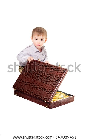 The child is sitting with a suitcase full of gold ingots, isolated on a white background - stock photo