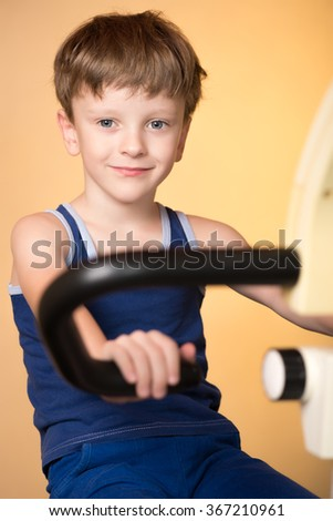 The child is trained on a stationary bike . Leads a healthy lifestyle. The boy develops muscles . Tired and sweaty . Sport generation.