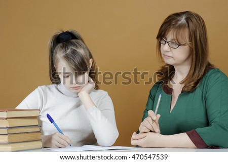 The child makes school lessons under the supervision of her mother.