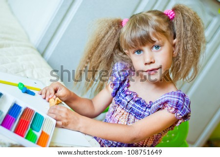 The child molds from clay in the interior - stock photo